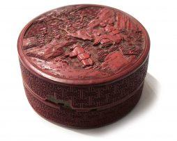 Boite en laque de Pékin de forme ronde décorée en léger relief. Sur le couvercle, un sage sous un arbre avec deux disciples: l'un porte sur l'épaule une branche avec deux pêches de longévité; l'autre montre à son maitre un linghzi accroché à un rocher.